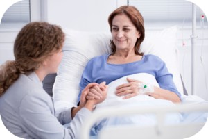 Woman in hospital bed talking to healthcare professional